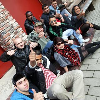 Zehn Jugendlichen sitzen zusammen und halten die Daumen hoch.