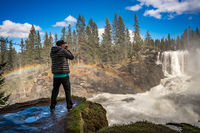 Nature photographer tourist with camera shoots while standing Ristafallet waterfall in Sweden.