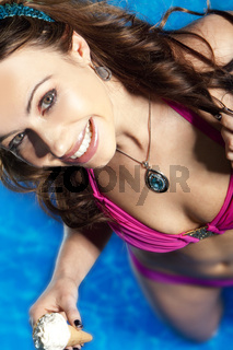 High angle portrait of smiling young woman in swimming pool with ice cream.