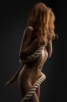 Nude woman rope wrapped around body cropped shot