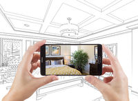 Hands Holding Smart Phone Displaying Photo of Bedroom Drawing Behind