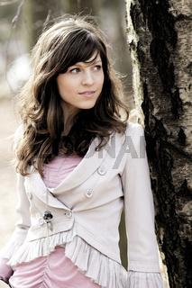 junge Frau laechelt draussen in der Natur am Baum