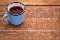 metal cup of hot tea on a rustic picnic table