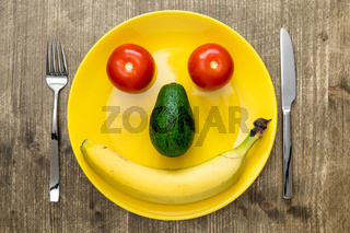 Smiling face from vegetables and fruits on plate