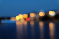 Blurred city lights with bokeh effect reflected on water surface.
