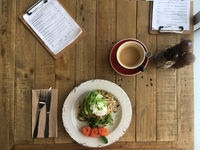 Top View zucchini fritters poached eggs avocado salmon and bulletproof coffee