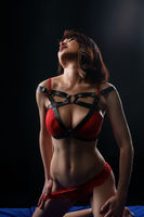 Sexy woman in red bdsm style lingerie in studio