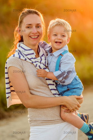 Woman and child having fun outdoors in sunset sunlight