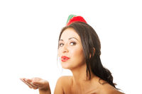 Portrait of a woman wearing elf clothes blowing kiss, looking at the camera