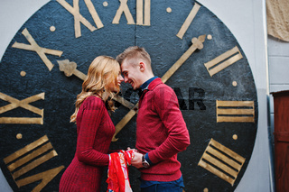 Young beautiful stylish fashion couple in a red dress in love story at the old city, play with shawl background big clock