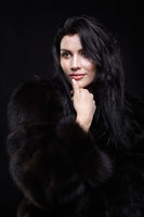 Portrait of a young brunette woman with long black hair dressed in a fur coat on black