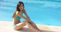 Exotic brunette wearing blue bikini sits by pool