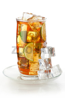 Glass of iced tea with ice cubes, lime and mint, covered with water drops