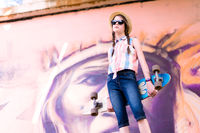 Young skateboard girl holding her longboard outdoors in front of graffiti mural
