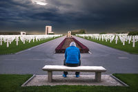 Man contemplating in a memorial cemetery
