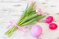 tulips with easter eggs and candle in pink