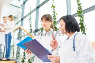Ärztin und junge Kollegin besprechen Patientenakte