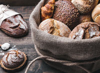 Delicious freshly baked bread inside a sack on wooden background