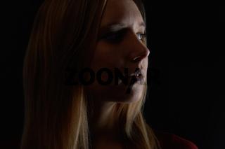 Nachdenkliche junge blonde Frau schaut zur Seite
