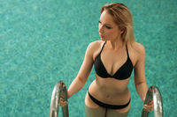 Slim sexy blonde in a swimming pool cropped view