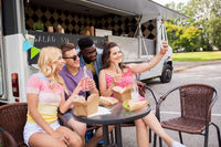 happy young friends taking selfie at food truck