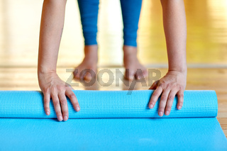 woman hands rolling yoga mat at gym or studio