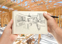 Male Hands Holding Pen and Pad of Paper with Custom Kitchen Illustration Inside Construction Framing.