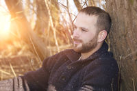 a thoughtful bearded man in the forest sunset