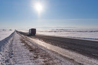 Bus on winter road and trees under snow in Altai