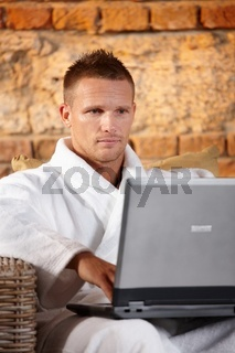 Handsome man with computer in bathrobe
