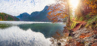 Path on Alpsee lake shore in autumn decor