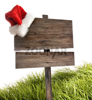 Weathered wooden sign with santa hat and grass on white