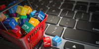Shopping basket with domain nameson computer keyboard. Internet communication and e-business concept.