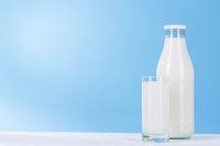 Flasche und Glas Milch auf hell blau Hintergrund.