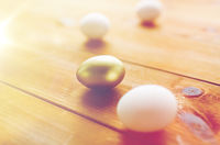 close up of golden and white easter eggs on wood