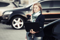 Young fashion business woman with laptop at the car