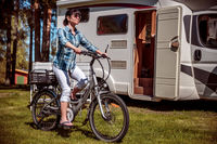Woman on electric bike resting at the campsite