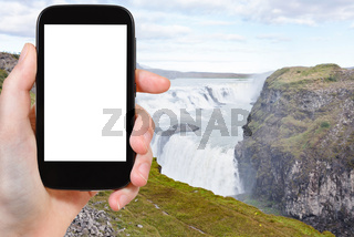 tourist photographs Gullfoss waterfall in canyon