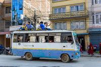 People travel on top of a bus in Kathmandu, Nepal