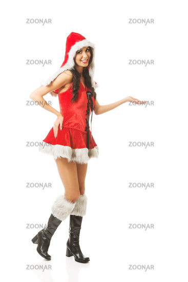 Full length woman holding something invisible in right hand wearing santa clothes