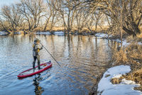 Stand up paddler poling on shallow river