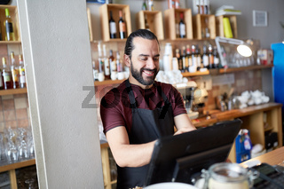 happy man or waiter at bar cashbox