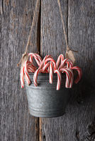 A bucket of candy canes for Christmas hanging against a rustic wood wall.