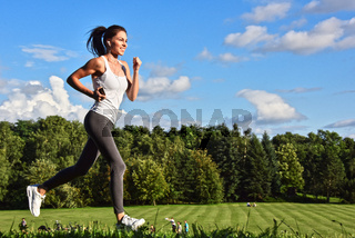 Young woman running in the park during sport training.