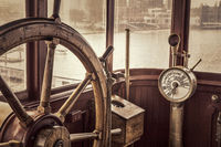 vintage ship steering wheel in sepia toning