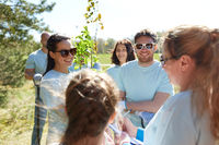 group of volunteers with tree seedlings in park