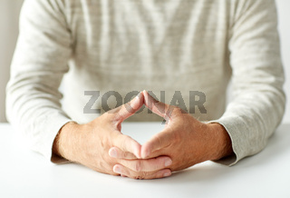 close up of old man hands in triangle of power