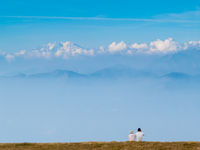 couple of young tourists in the Swiss mountains, observe the landscape of the Alps in front of them