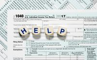 Macro close up of 2017 IRS form 1040 with HELP letters