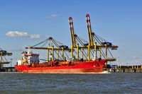 Freight ship in front of port facilities and cranes